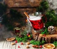 Ποτήρι του καυτού θερμαμένου κρασιού για το νέο έτος με τα συστατικά για το μαγείρεμα, τα καρύδια και τις διακοσμήσεις Χριστουγέν Στοκ Φωτογραφία