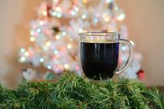 Ποτήρι του καυτού κακάου μπροστά από το άσπρο χριστουγεννιάτικο δέντρο με τα χρωματισμένα φω'τα στοκ εικόνες με δικαίωμα ελεύθερης χρήσης