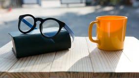 Ποτήρι του καφέ και των γυαλιών στον ξύλινο πίνακα Στοκ φωτογραφία με δικαίωμα ελεύθερης χρήσης