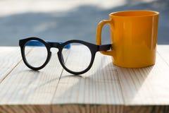 Ποτήρι του καφέ και των γυαλιών στον ξύλινο πίνακα στοκ εικόνα