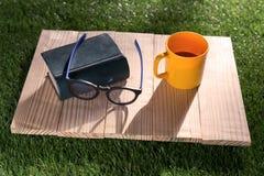 Ποτήρι του καφέ και των γυαλιών στον ξύλινο πίνακα Στοκ Εικόνες