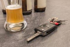 Ποτήρι του κλειδιού μπύρας και αυτοκινήτων στον γκρίζο πίνακα Στοκ Εικόνα