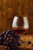 Ποτήρι του κονιάκ και μια δέσμη των σταφυλιών Στοκ φωτογραφία με δικαίωμα ελεύθερης χρήσης