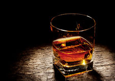 Ποτήρι του κονιάκ σε ένα τετραγωνικό γυαλί στοκ φωτογραφία