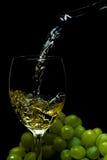 Ποτήρι του κρασιού, σταφύλια, κρασί, που ρέει από ένα μπουκάλι, μαύρο υπόβαθρο Στοκ φωτογραφίες με δικαίωμα ελεύθερης χρήσης