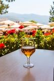 Ποτήρι του κρασιού στον ξύλινο πίνακα στο υπόβαθρο της παραλίας umbrell στοκ εικόνες με δικαίωμα ελεύθερης χρήσης