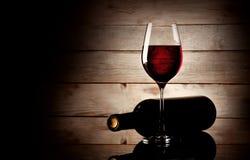 Ποτήρι του κόκκινου κρασιού και του μπουκαλιού που βρίσκονται στην πλευρά του Στοκ Φωτογραφία