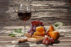 Ποτήρι του κόκκινου κρασιού, κηρήθρα, σταφύλια σε ένα ξύλινο υπόβαθρο Στοκ φωτογραφία με δικαίωμα ελεύθερης χρήσης