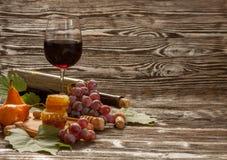 Ποτήρι του κόκκινου κρασιού, κηρήθρα, σταφύλια σε ένα ξύλινο υπόβαθρο Στοκ Εικόνες