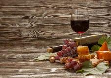Ποτήρι του κόκκινου κρασιού, κηρήθρα, σταφύλια σε ένα ξύλινο υπόβαθρο Στοκ Εικόνα