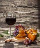 Ποτήρι του κόκκινου κρασιού, κηρήθρα, σταφύλια σε ένα ξύλινο υπόβαθρο Στοκ Φωτογραφία