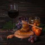 Ποτήρι του κόκκινου κρασιού, κηρήθρα, σταφύλια Στοκ Φωτογραφία
