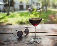 Ποτήρι του κόκκινου κρασιού μπροστά από το θερινό ναυπηγείο Στοκ εικόνα με δικαίωμα ελεύθερης χρήσης