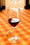 Ποτήρι του κόκκινου κρασιού στο αγροτικό τραπεζομάντιλο Στοκ Φωτογραφία