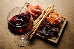 Ποτήρι του κόκκινου ξηρού κρασιού και διάφορα είδη θεραπευμένων κρεάτων σε έναν ξύλινο πίνακα Στοκ Εικόνες