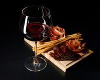 Ποτήρι του κόκκινου ξηρού κρασιού και διάφορα είδη θεραπευμένων κρεάτων στο μαύρο υπόβαθρο Στοκ εικόνα με δικαίωμα ελεύθερης χρήσης