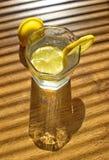 Ποτήρι του νερού με τα κομμάτια του λεμονιού στον πίνακα Στοκ εικόνα με δικαίωμα ελεύθερης χρήσης