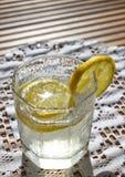 ποτήρι του νερού με τα κομμάτια του λεμονιού στο τραπεζομάντιλο Στοκ φωτογραφία με δικαίωμα ελεύθερης χρήσης