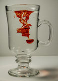 Ποτήρι του νερού με την κόκκινη πτώση στοκ φωτογραφία με δικαίωμα ελεύθερης χρήσης