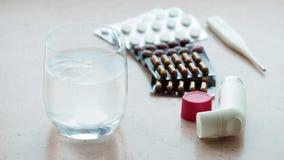 Ποτήρι του νερού με τη ζωηρή ταμπλέτα και τα διάφορα φάρμακα φιλμ μικρού μήκους