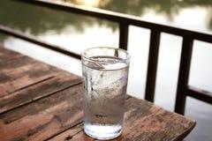 Ποτήρι του νερού σε ένα ξύλινο γραφείο κοντά στη λίμνη στοκ εικόνες