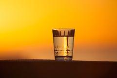 Ποτήρι του νερού στο υπόβαθρο του όμορφου ηλιοβασιλέματος εκλεκτικός Στοκ φωτογραφίες με δικαίωμα ελεύθερης χρήσης