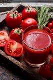 Ποτήρι του νόστιμου οργανικού χυμού ντοματών και των φρέσκων ντοματών και χορτάρια στον ξύλινο δίσκο στο αγροτικό ύφος Στοκ Εικόνες