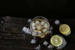 Ποτήρι του ουίσκυ με τον πάγο σε ένα ξύλινο υπόβαθρο με τον πάγο, τοπ άπ στοκ φωτογραφία με δικαίωμα ελεύθερης χρήσης