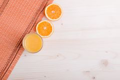 Ποτήρι του πορτοκαλιού φρέσκου χυμού σε έναν ελαφρύ πίνακα και της πορτοκαλιάς κορυφής αυτιών Στοκ φωτογραφία με δικαίωμα ελεύθερης χρήσης