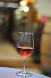 Ποτήρι του ροδαλού κρασιού σε έναν πίνακα Στοκ Φωτογραφίες