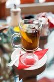 Ποτήρι του τσαγιού με το λεμόνι, τα ραβδιά κανέλας, το αστέρι γλυκάνισου και τα φύλλα μεντών μεντών Στοκ Εικόνα
