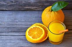Ποτήρι του φρέσκου χυμού από πορτοκάλι, των ώριμων πορτοκαλιών φρούτων και των φετών στον αγροτικό ξύλινο πίνακα Πρόσφατα συμπιεσ Στοκ εικόνες με δικαίωμα ελεύθερης χρήσης