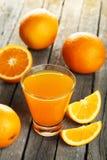 Ποτήρι του φρέσκου χυμού από πορτοκάλι στο ξύλινο υπόβαθρο Στοκ Φωτογραφίες
