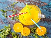 Ποτήρι του χυμού από πορτοκάλι άνωθεν στην εκλεκτής ποιότητας ξύλινη άποψη επιτραπέζιων κορυφών Στοκ Φωτογραφία