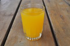 Ποτήρι του χυμού από πορτοκάλι στο ξύλινο υπόβαθρο στοκ εικόνα