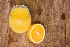 Ποτήρι του χυμού από πορτοκάλι με μισό πορτοκάλι Στοκ Φωτογραφίες