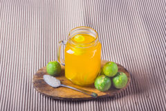 Ποτήρι του χυμού από πορτοκάλι με το άχυρο και των φετών στον ξύλινο πίνακα στοκ εικόνα με δικαίωμα ελεύθερης χρήσης