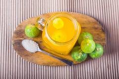 Ποτήρι του χυμού από πορτοκάλι με το άχυρο και των φετών στον ξύλινο πίνακα στοκ εικόνες