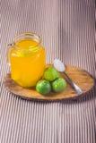 Ποτήρι του χυμού από πορτοκάλι με το άχυρο και των φετών στον ξύλινο πίνακα στοκ φωτογραφία