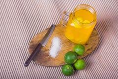 Ποτήρι του χυμού από πορτοκάλι με το άχυρο και των φετών στον ξύλινο πίνακα στοκ εικόνα