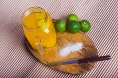 Ποτήρι του χυμού από πορτοκάλι με το άχυρο και των φετών στον ξύλινο πίνακα Στοκ φωτογραφία με δικαίωμα ελεύθερης χρήσης