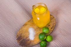 Ποτήρι του χυμού από πορτοκάλι με το άχυρο και των φετών στον ξύλινο πίνακα στοκ φωτογραφίες