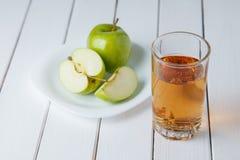 Ποτήρι του χυμού και των μήλων μήλων στον ξύλινο πίνακα, στο υπόβαθρο φύσης Στοκ εικόνα με δικαίωμα ελεύθερης χρήσης