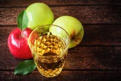 Ποτήρι του χυμού μήλων με τα κόκκινα και πράσινα μήλα στο ξύλινο υπόβαθρο Στοκ φωτογραφία με δικαίωμα ελεύθερης χρήσης