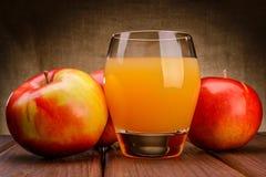 Ποτήρι του χυμού μήλων με τα μήλα Στοκ Φωτογραφία