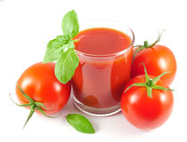 Ποτήρι του χυμού ντοματών με τις ντομάτες και τα φύλλα βασιλικού Στοκ Εικόνα