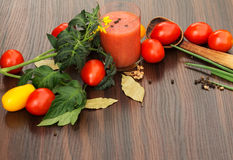 Ποτήρι του χυμού ντοματών με τις ντομάτες στον πίνακα Στοκ Φωτογραφία