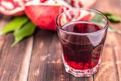 Ποτήρι του χυμού ροδιών με το ρόδι στο υπόβαθρο, ο στοκ εικόνα με δικαίωμα ελεύθερης χρήσης