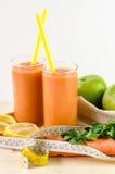 Ποτήρι του χυμού φρούτων με το πορτοκάλι, τα καρότα και την πιπερόριζα στοκ εικόνα