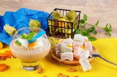 Ποτήρι των φρούτων milkshake και της τουρκικής απόλαυσης Γλυκά θερινά πρόχειρα φαγητά σε ένα ζωηρόχρωμο υπόβαθρο Φρέσκα και εξωτι Στοκ Φωτογραφία